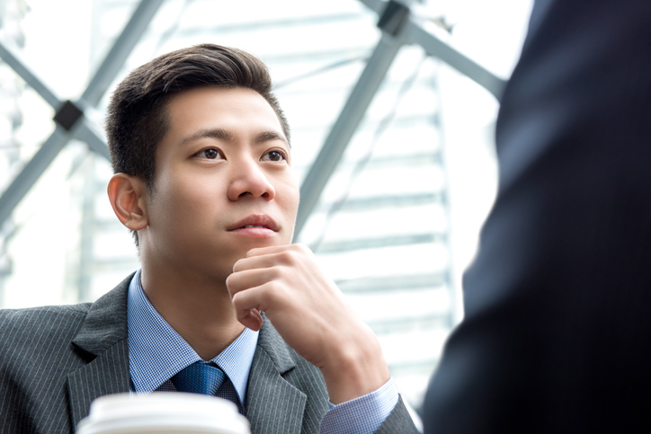 Asian Chinese businessman listening to his partner with eye contact